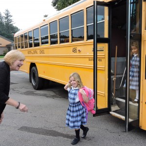 Mrs. Wagner welcomes students as they come off the bus.